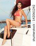 Portrait of a gorgeous long-haired brunette in stylish swimsuit sitting on a sailing yacht. Sunny and windy summer day. Bikini fashion. Outdoor shot - stock photo