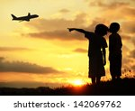 Two kids silhouette on meadow looking at airplane in air - stock photo