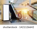 Small photo of blank showcase billboard or advertising light box for your text message or media content with escalator in modern department store shopping mall, shopping center, commercial and marketing concept