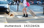 Woman crossing street, traffic in background - stock photo