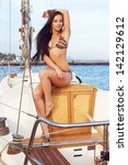 Portrait of a gorgeous long-haired brunette in stylish swimsuit with awesome tan sitting on the aft of a sailing yacht. Sunny summer day. Bikini fashion. Copy-space. Outdoor shot - stock photo
