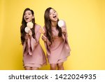 charming twins closing eyes... | Shutterstock . vector #1422024935