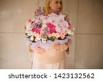 Small photo of Girl holding a huge spring box of tender multicolored pink flowers decorated with green leaves