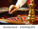 the croupier holds a roulette...