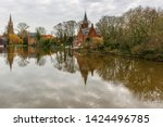 The famous Minnewater lake or Lake of Love, in the historic city center of Bruges with a reflection of a medieval castle and the Our Lady church, Bruges, West Flanders, Belgium.