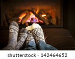 feet in wool socks warming by... | Shutterstock . vector #142464652