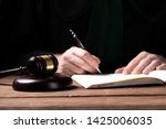 Small photo of A lawyer looking at the penal code with magnifying glass - searching for the right sentence