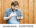 Small photo of Serious bearded man cleans glasses by rubbing them with the help of his shirt and squinting, looking at the camera with hostility. Isolated on the background of an old wooden wall. Close-up.