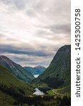 Calm river flowing amidst green mountain peaks against cloudy sky in evening in Norway