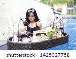 poolside breakfast asian woman...   Shutterstock . vector #1425327758