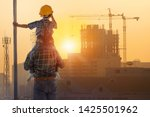 Asian boy on father's shoulders with background of new high buildings and silhouette construction cranes of evening sunset, father and son concept - stock photo