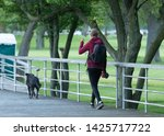 Stock photo unknown woman takes a walk at the park with her backpack and dog 1425717722