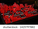 red candles in rows  on dark... | Shutterstock . vector #1425797882