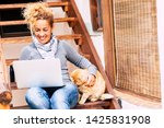 Stock photo cheerful pretty middle age woman work with laptop computer outdoor at home with nice cat near her 1425831908