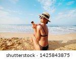 beautiful woman apply sun cream ...   Shutterstock . vector #1425843875