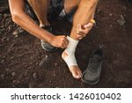 Small photo of Man bandaging injured ankle. Injury leg while running outdoors. First aid for sprained ligament or tendon. Close-up on dark background.