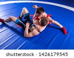 Two young man  wrestlers in red and blue uniform wrestling  on a blue wrestling carpet in the gym. Grappling.