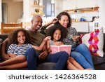 family sitting on sofa at home... | Shutterstock . vector #1426364528