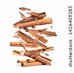 Small photo of Cinnamon sticks are falling down on a pile,isolated on a white background