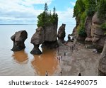 Small photo of Hopewell Cape, New Brunswick - July, 2018: Tourists must leave the ocean floor as the tide comes in among the flowerpot rocks.