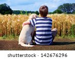 Stock photo boy with pet dog corn field in background 142676296