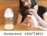 Small photo of Bottle with breast milk on background of mother holding in her hands and using hand help a baby newborn belch burping after breastfeeding milk. Maternity and baby care. Mother parenting