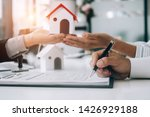 Small photo of Real estate agents submit documents for customers to sign for a sale contract,real estate concept.