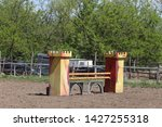 Image of show jumping poles on the training field. Wooden barriers for jumping horses as a background. Colorful photo of equestrian obstacles. Empty field for horse jumping event competition