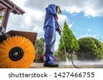 Men Wearing Industrial Wet Coat Cleaning Residential Driveway using Power Pressure Washer. - stock photo
