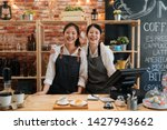 Small photo of Small startup business owner concept. two successful young baristas women standing in bar counter in cafe. happy coffeehouse waitresses in aprons smiling confidently to camera in coffee shop.