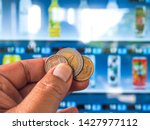hand with coin to vending... | Shutterstock . vector #1427977112