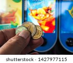 hand with coin to vending... | Shutterstock . vector #1427977115