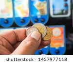 hand with coin to vending... | Shutterstock . vector #1427977118