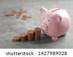 piggy bank and coins on grey... | Shutterstock . vector #1427989028