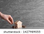 woman putting coin near house... | Shutterstock . vector #1427989055