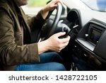 Car interior. Depicted a man behind the wheel. He holds the phone in his hand. Selective focus. - stock photo