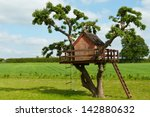 Beautiful creative handmade tree house for kids in backyard of a house - stock photo
