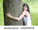 Young Woman Hugging A Big Tree