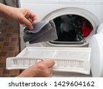 Small photo of Woman's hand removing lint from fluff filter of the tumble dryer on blurred background of clothes dryer with washed clothing. Laundry processes, Cleaning and care concept. (close up, selective focus)