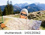 Young Woman Hiker Reading Map...