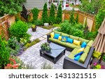 Small photo of A beautiful small, urban backyard garden featuring a tumbled paver patio, flagstone stepping stones, and a variety of trees, shrubs and perennials add colour and year round interest.