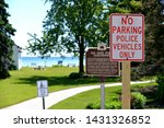 No Parking Police Vehicles Only sign at the Wind Point Wisconsin Police Station at the Lighthouse park along the shores of Lake Michigan with out of focus background and other signs.