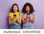 Small photo of Photo of happy diverse female friends ignore live communication, chat in web blog via cell phones, gaze with positive expressions at screens, wear casual clothes, stand shoulder to shoulder.