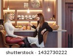 Stock photo two charming young girls are drinking fresh fruit juice and talking while sitting on bar stools 1432730222