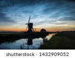 Noctilucent clouds (NLCs) or polar mesospheric clouds, looking north at midsummer night. Classic dutch scene with a canal and windmill silhouet against the evening sky.