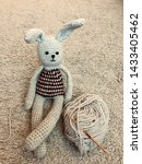 Stock photo knitted hare gray hare crocheted amigurumi on a gray background with a lying skein of 1433405462