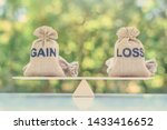 Small photo of Capital investment gain and loss, financial concept : Gain and loss bags on a basic balance scale, depicts balancing between profit and loss while managing assets e.g bonds, stocks, derivatives, ETFs