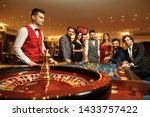 Group happy friends make bets gambiling at the roulette table in the casino. - stock photo