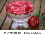 Stock photo a lot of bright rose petals in cold water a beautiful wine glass water droplets on misted glass a 1433832302