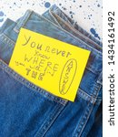 Small photo of Jeans pocket with inspirational quote card on yellow background. You never know where you will find the answer. Self motivation.